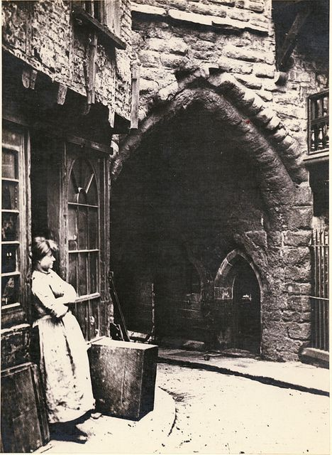 Black Gate [c1880] Black Gate, close-up of the gateway with a woman leaning against a shop doorway