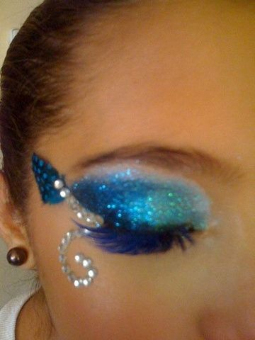 Shimmering blue eye shadow with blue eye lashes accented with a feather and crystal scroll.