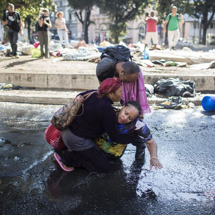 """A woman is helped after she was hit and wounded by water cannons used by Italian police to disperse refugees who were evicted from a palace in the center of Rome on Aug. 24, 2017. The U.N.'s refugee agency voiced """"grave concern"""" over the eviction of 800 people from a Rome building used mainly by asylum seekers and refugees from Eritrea and Ethiopia. Almost 200 people who were expelled from the building have been sleeping on the streets since Aug. 19. Photograph by Christian…"""