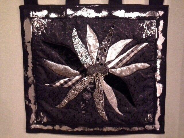 Silver/black flower wall quilt for Louise by Kath Cole 2015. Reverse appliqué, foiling.