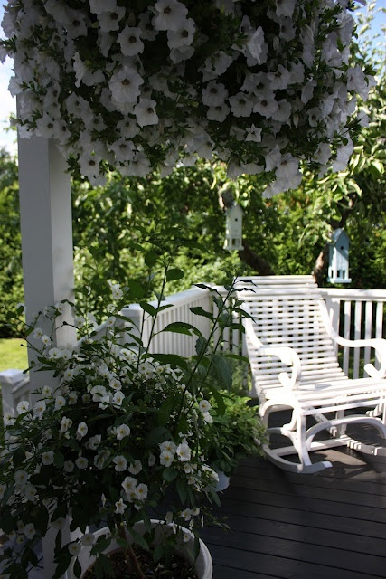 pretty white hanging flower baskets and white porch furniture