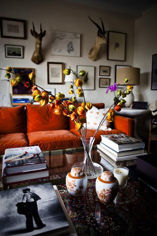 Orange sofa dominates this living room, with drama on the walls to balance it. Ruthie Sommers