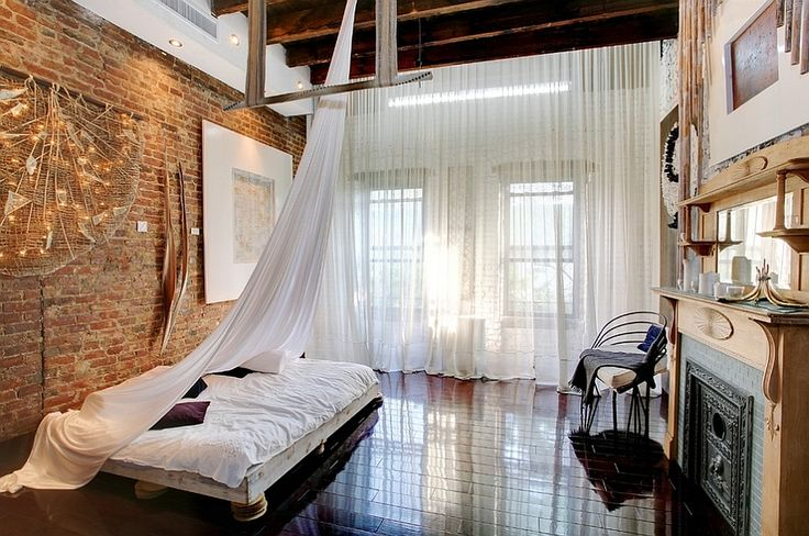 Loft-style bedroom with high ceiling, wooden beams and low-slung decor [Photography: Laura Dante]