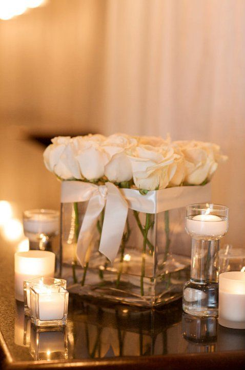Square Vases with all white roses make a beautiful wedding . perhaps we can use white flowers and blue ribbon