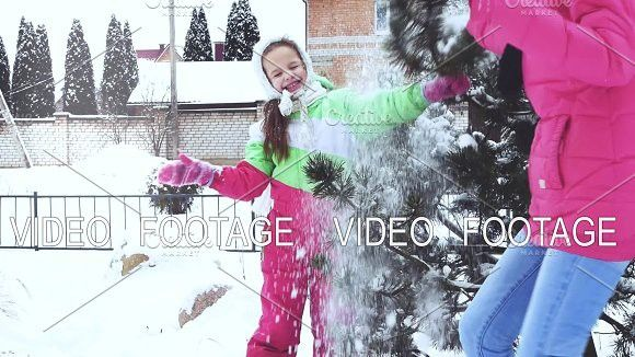 Fun, tree, snow. Mother shakes tree and snow falls on little girl, who is surprised and very emotional about it. #family #daughter
