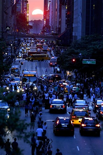 July 12, 2012: Under clear skies, crowds turn out to see stunning views of Manhattanhenge in New York on July 11. This Big Apple phenomenon occurs when the setting sun aligns with the city's east-west street grid. (© Julio Cortez/AP)