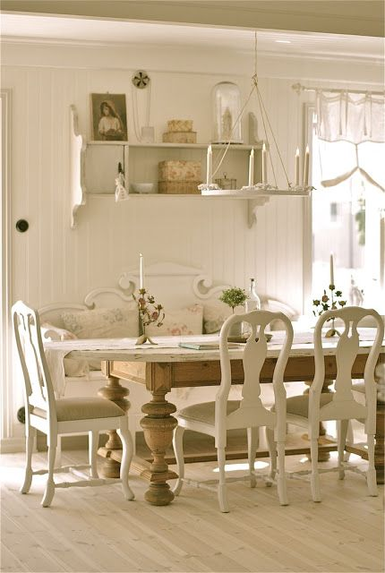 Pretty Swedish country dining room with a large Swedish pine sofa. The pillows and cushion are covered in fabrics with muted colored patterns.