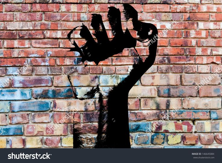 Retro style clenched fist held high in protest against grunge concrete wall background indicating revolution or aggression. Graffiti fist.