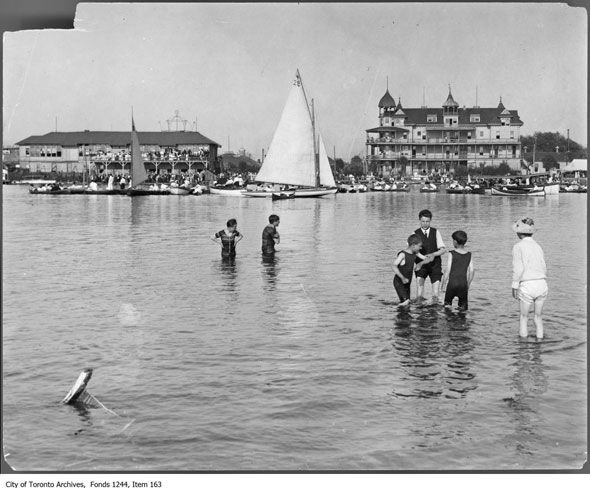 toronto long weekend - Kids paddling at Hanlan's Point in 1907. Hanlan's Hotel and regatta in the background