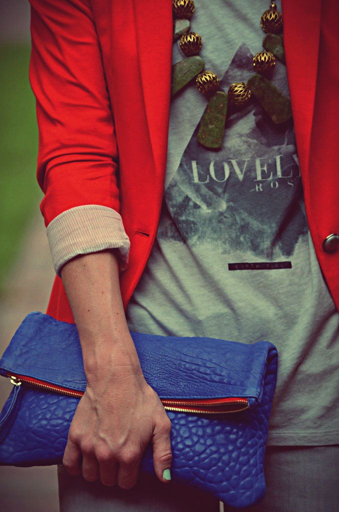 Red blazer, graphic tee, statement necklace, and vibrant cobalt blue clutch.
