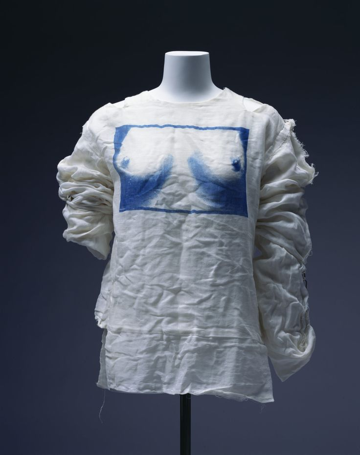 Shirt, ca. 1977 | Designers: Vivienne Westwood and Malcolm McLaren | Brand: Seditionaries | Materials: white cotton gauze with photo print of female breasts; strap; velcro; metal | At the end of the 1970s, young people gathered on King's Road in London to express social opposition. They challenged to show their protestation by their fashion: ripped clothes, safety pins, bondage styles and multi-colored hair. They were called 'punks' | The Kyoto Costume Institute