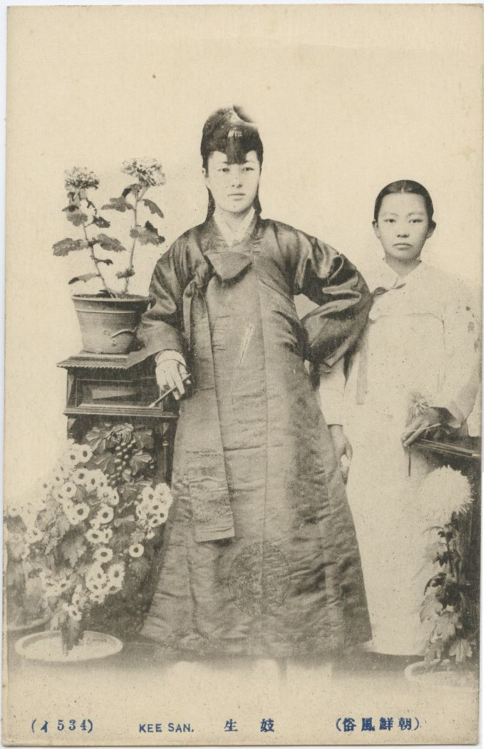 "Kee San=""Kisaeng"" or ""Gisaeng."" Most postcards of kisaeng from 1900-1910 show those who worked at the royal palace or various government offices (known as gwan'gi) in colorful robes or dance. After the gwan'gi system was abolished in 1908, images of kisaeng changed their focus to closeups of faces and physical features (Kwon 2005, pp. 231-232). Different forms of dress began to appear in photos after the 1910s. 1918-1918 East Asia - Imperial Postcard Collection, Lafayette College."
