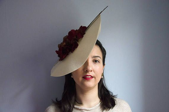Ivory disk fascinator with phaisant feather and coffee and bugundy hydrangeas over a satin headband. This fascinator is very flattering adding some height and protectin from the sun. It adds a hing of mistery hidding a bit the face. The disk is a bit flexible so it can be adapted to your taste. The feather and hydrangeas may differ upon availability. Please ask for details. It can be customised to your taste changing colours and shape. Availability of items change with time. Let me know how…