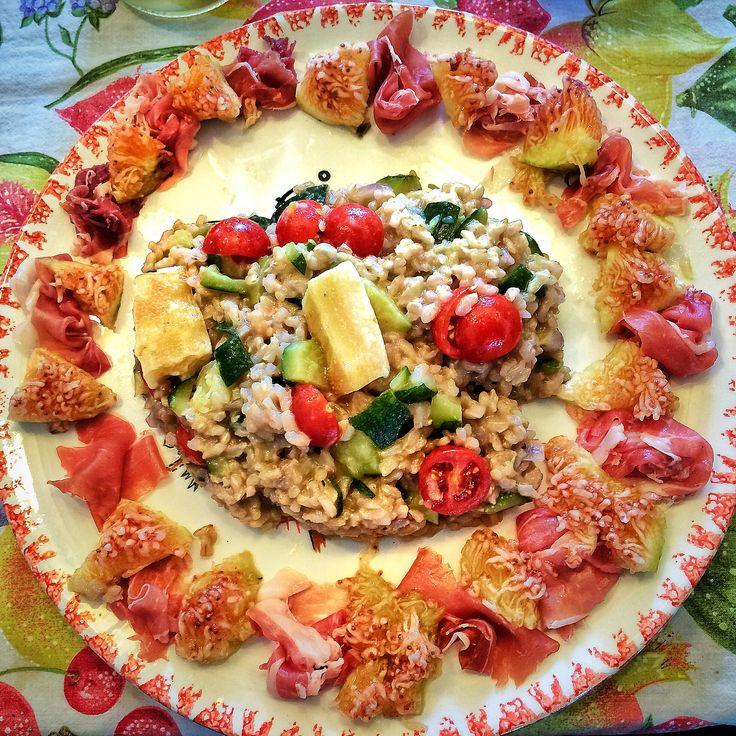 Riso integrale con cipolle rosse, zucchine e cubetti di parmigiano semifuso, circondato da una corona di prosciutto crudo dolce e fichi