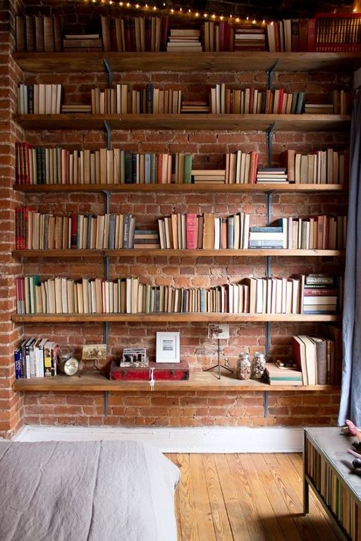 This Exposed Brick Wall Behind These Book Shelves Adds A