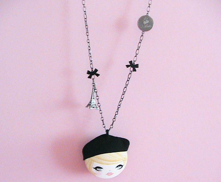 This unique hand painted necklace would make a nice accent on your every day wearing.  •About 2 wooden dome, hand painted with acrylic paints and gloss varnish •Hat made with genuine ultra suede •Genuine ultra suede backing •Eiffel tower charm, Jtaime metal and black metal bow charms •Gun metal plated bail •About 24 in total length with gun metal chain