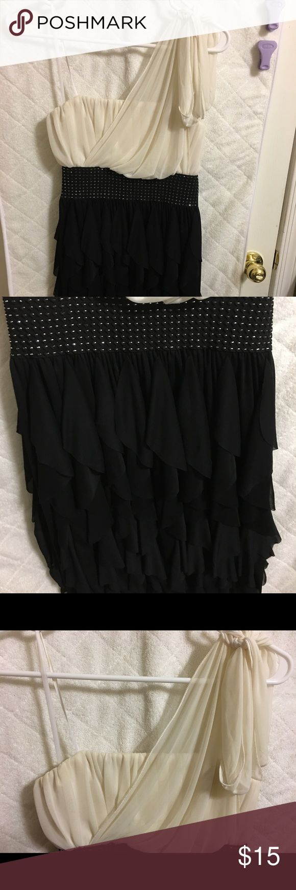 Black and White Homecoming Dress Black frilled skirt with a sparkly band around the waist and a pretty white flowing top with one shoulder tie. Also has elastic grip around the top inside to prevent slippage. Worn once to a homecoming dance. Roberta Dresses Prom