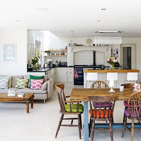 Kitchen diner with white walls, grey sofa, wooden table and colourful chair cushions