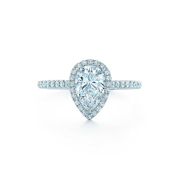 Bead-set diamonds surround a striking pear-shaped diamond in this unusual platinum design.