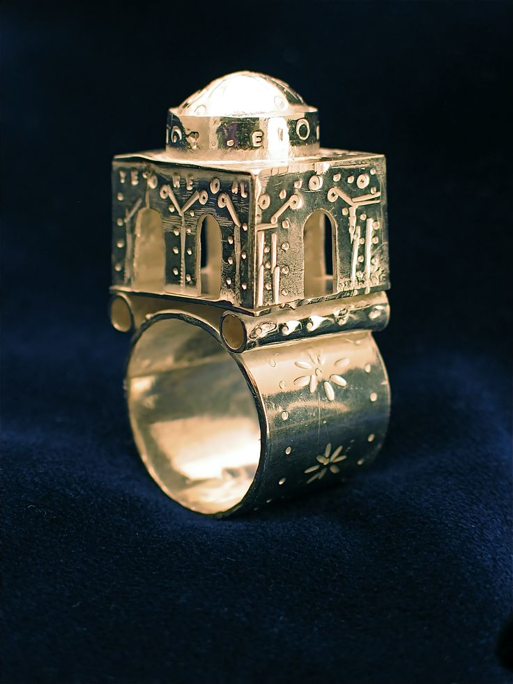 "Jewish Wedding Ring, Ethan Wilcox, 2008, sterling silver, 1"" by 1"" by 2""    This is a traditional Jewish wedding ring. The building represents the home the new couple is about to create and the Second Temple in Jerusalem, who's destruction marked the beginning of the diaspora. The letters on the piece spell out a transliteration of the Shema, the holiest prayer in Judaism"