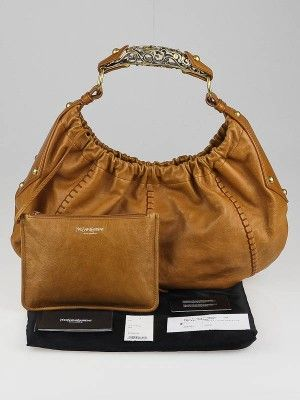 Don't miss out on your chance to own this rare Yves Saint Laurent Camel Leather Vincennes Mombasa Hobo Bag. It features a chic hobo design made with gorgeous leather and a metal horn-shaped handle with exquisite details. The perfect bag for any stylish fashionista. Retail price is $1950.