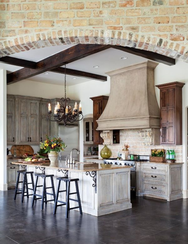 An abundance of texture—reclaimed bricks on the arched entry into the kitchen and and the kitchen backsplash as well as hand-hewn beams crowning the kitchen ceiling—imbues warmth and comfort in this European-style space. - Photo: Nancy Nolan / Design: Mona Thompson and Talena Ray