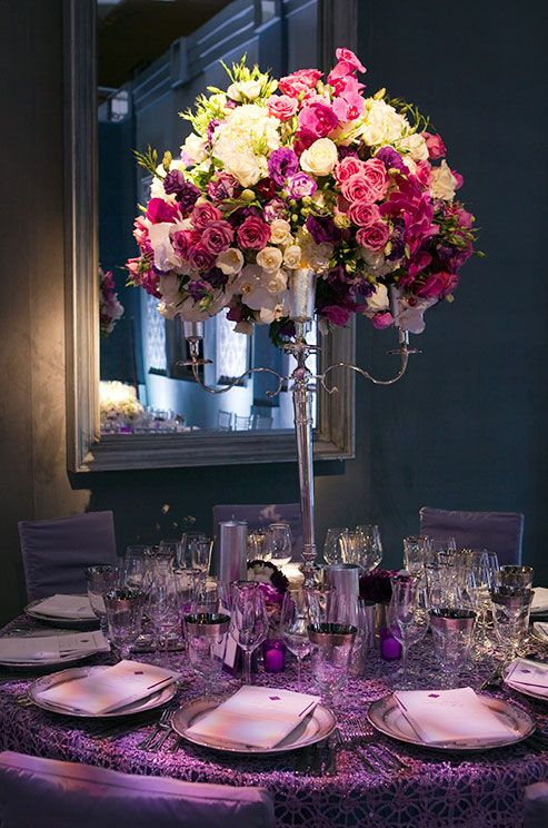 A silver candelabra is packed with roses and orchids, making for one glamorous wedding centerpiece.