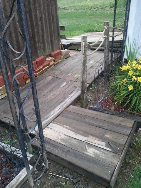 Old pallets and fence boards turned into deck covering mud ...