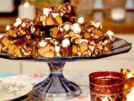 Leilas Rocky Road    Ingredienser    12 kakor  600 g mörk kvalitetschoklad 70 %   2 påsar dumlekola   2 nävar minimarshmallows   3 dl salta jordnötter   1 dl skalade pistagenötter     Gör så här    1. Smält chokladen på låg värme i vattenbad (i en skål över kokande vatten).  2. Blanda samtliga ingredienser.  3. Fyll smeten i en plåt, cirka 3 cm tjock och låt stelna i kylskåp.  4. När kakan har stelnat, skär upp den i stänger.