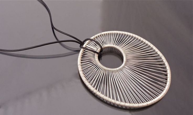 ''OH'' Pendant by Tana Acton. This light weight pendant is woven from one continuous filament of wire. It comes on a waxed linen cord that can be adjusted to the level where you prefer to wear it, long or close to the neck.
