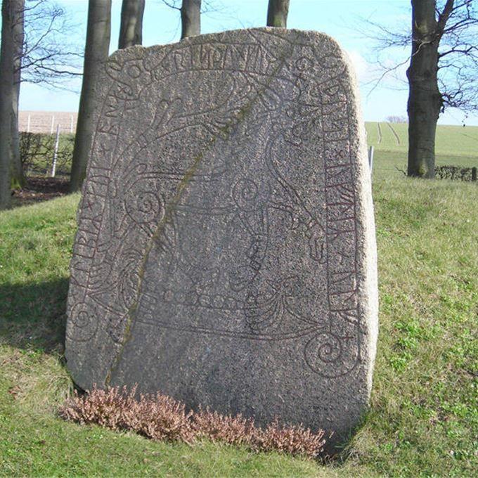 På en gravhög vid Tullstorps kyrka står en välbevarad runsten. Ett vargliknande djur och ett skepp med sköldar längs relingen inramas av runinskrift.