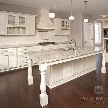 Creamy white kitchen by Kim Wiederholt Design featuring French rangehood, glass…