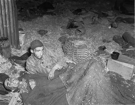 "Two survivors lie among corpses on the straw-covered floor of the ""Boelke Kaserne"", a barracks used for the disposal of dying inmates at the Nordhausen Concentration Camp."