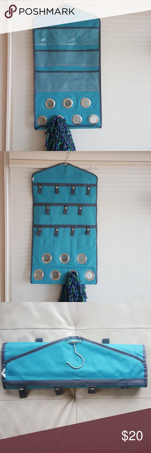 Scarf/accessory holder Hanging accessory holder with 7 open loops for scarves, 11 snapped loops for scarves or belts,  13 pocket cubbies for jewelry or small accessories.  Folds up sms had a built in hanger... so great for travel! Like new condition Accessories