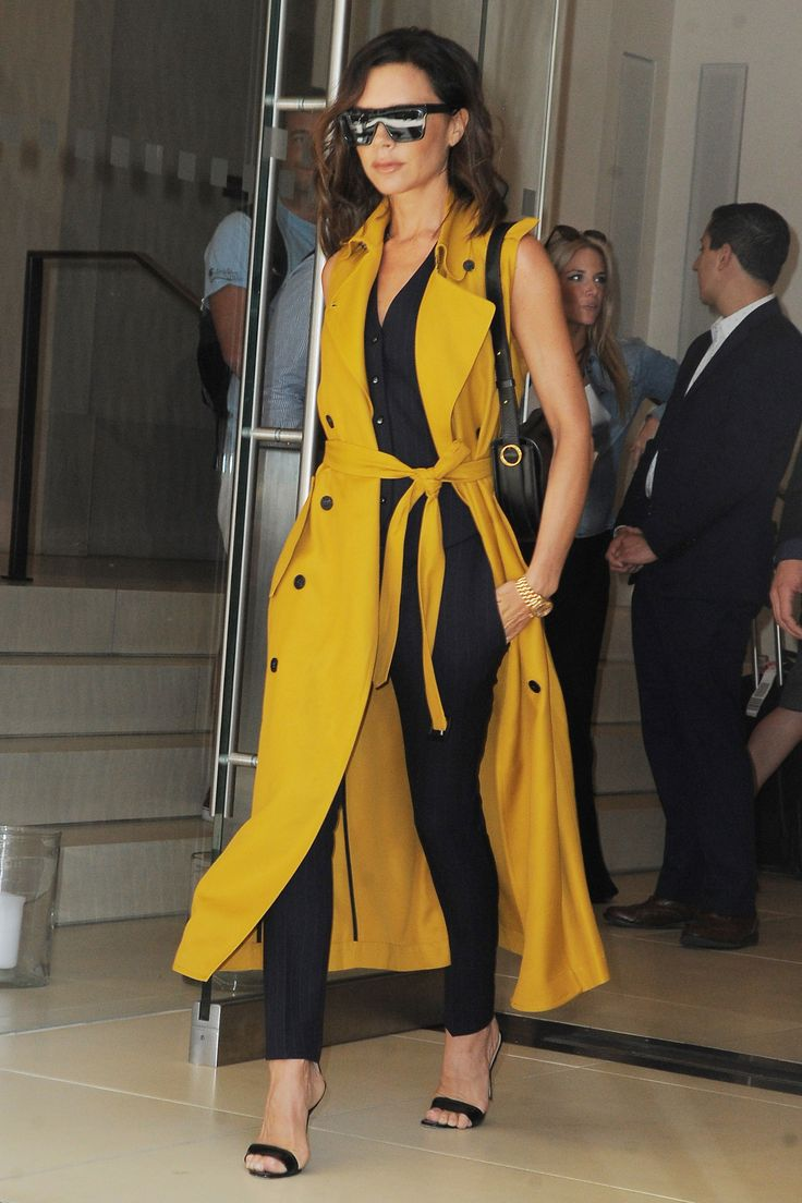 24 June Victoria Beckham added a sleeveless yellow duster coat onto her ensemble later in the day.   - HarpersBAZAAR.co.uk