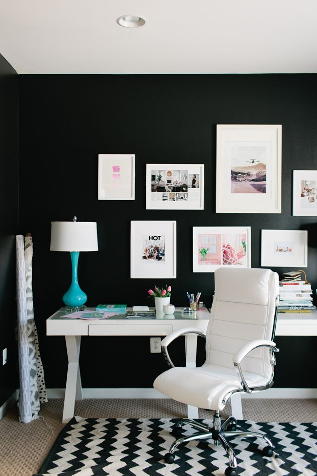Chic feminine office! White framed photographs and brightly colored accents pop off the black walls.