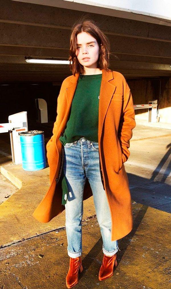 Street style: Sobretudo marrom combinando com a bota de veludo marrom? Pode sim!  Aproveite para misturar tons com o sueter verde e o jeans de lavagem clara.