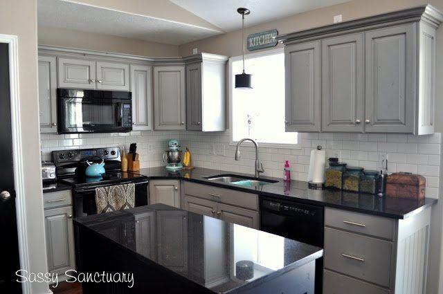 gray painted kitchen cabinets with black appliances, granite and white subway tile
