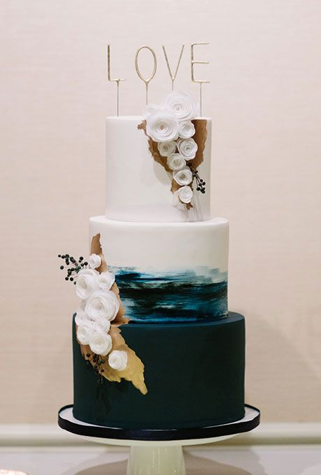 A modern three-tiered navy-and-white wedding cake with gold details and sugar flowers, created by Hey There, Cupcake.