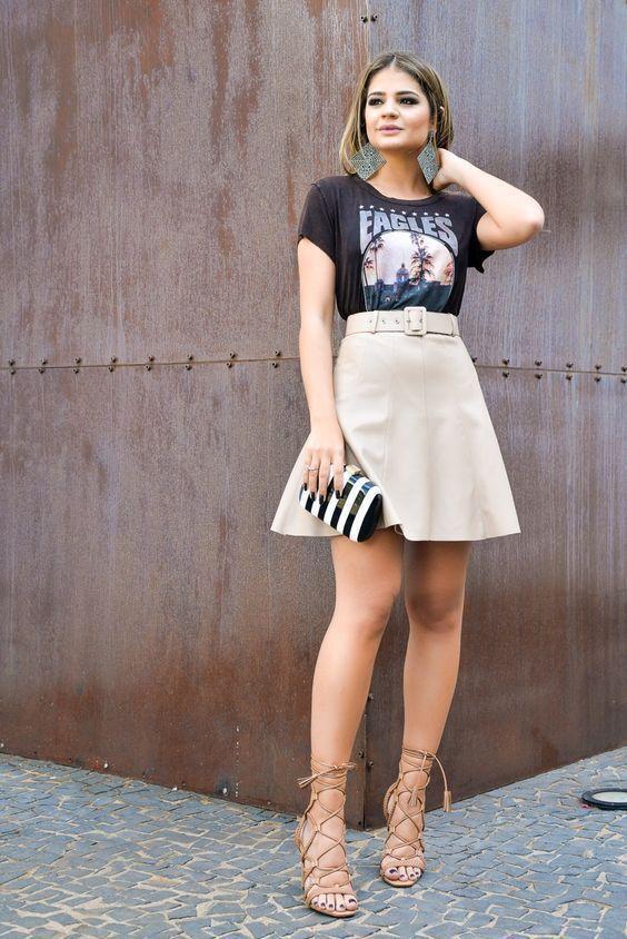 Como dar um toque descolado a peças delicadas. T-shirt de banda preta, saia de couro com rodada com cinto, cintura marcada, sandália gladiadira bege, lece up