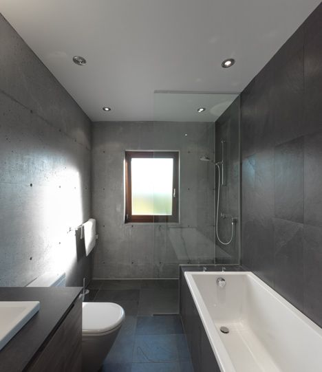 La Maison Beaumont by Henri Cleinge Architecte | polished stone walls in this clean and minimalistic 4-piece bathroom that includes a large walk-in shower with glass partition