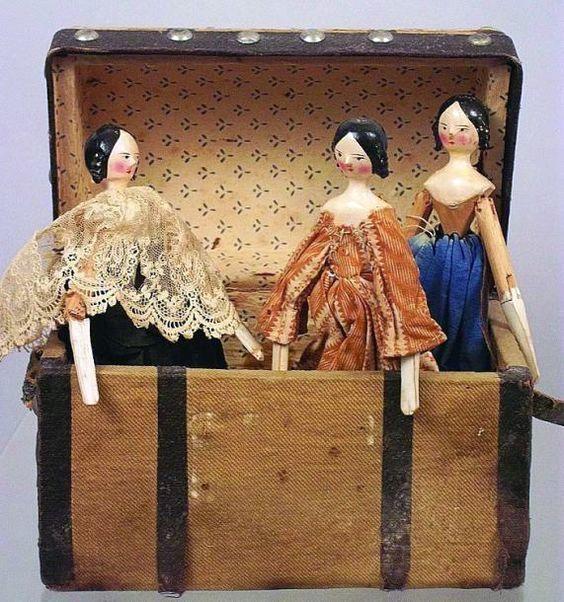 Charmante petite malle en bois avec trois poupées tout en bois et articulées de Nüremberg. H 15 cm.