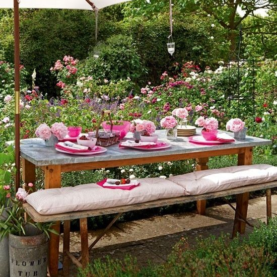 Pink garden tableware    This outdoor dining table is brimming with fuchsia crockery and peonies arranged in zinc pots and a garden bench by jamie_1