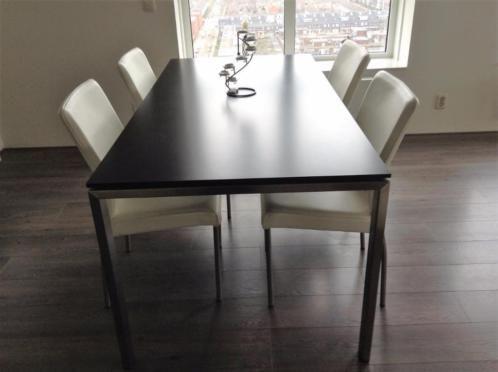 Moderne eettafel met roestvrij stalen poten en zwart kunsstofblad. 180 (L) x 90 (b) cm. Nieuwstaat. Indien gewenst samen met vier stoelen (roestvrij stalen poten met wit leren bekleding). De stoelen