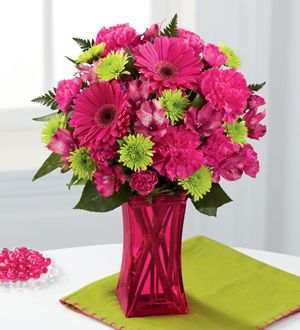 The FTD® Raspberry Sensation™ Bouquet comes straight from our simply irresistible Color Confection Collection. Blooming with sweetness and popping with extreme color, this flower bouquet consists of hot pink roses, carnations, gerbera daisies, Peruvian lilies and mini carnations offset by green button poms and lush greens. Presented in a pink glass vase to give it a raspberry look, this mixed flower arrangement is set to send your sweetest wishes. Perfect for Grandparents' Day!