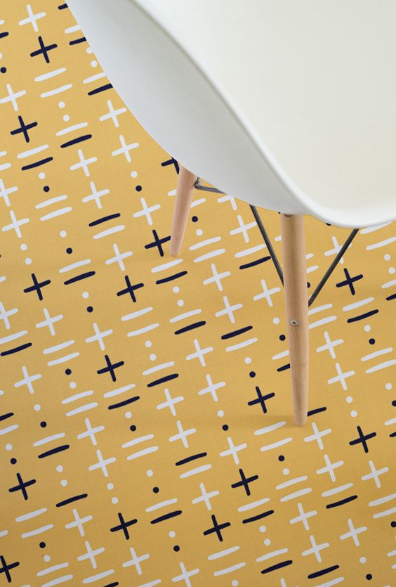 The Khan design features bold black and white lines and crosses against a stunning orange background, reminiscent of traditional African patterning.