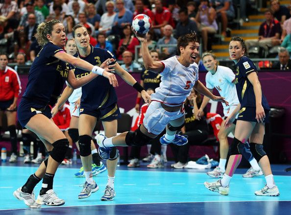 AAna Dokic  of Montenegro shoots past Begona Fernandez Molinos (L)  and Andrea Barno San Martin of Spain during the Women's Handball semifinal game between Spain and Montenegro on Day 13 of the London 2012 Olympic Games at the Basketball Arena on August 9, 2012 in London, England. - Olympics Day 13 - Handball