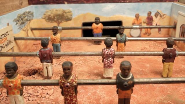 """Afrika Kicker: project for solidarity. Afrika Kicker è il calcio balilla africano che permette di raccogliere donazioni per l'iniziativa """"2 Euros Help"""". Il biliardino ha un fondo di sabbia irregolare e un albero in mezzo al campo, ai bordi del campo ci sono immagini di progetti sostenuti dalle donazioni. Il gioco è disponibile anche per i dispositivi mobili e su Facebook, in un design sorprendente africano. Per maggiori informazioni visita il sito afrika-kicker.de e partecipate numerosi!"""