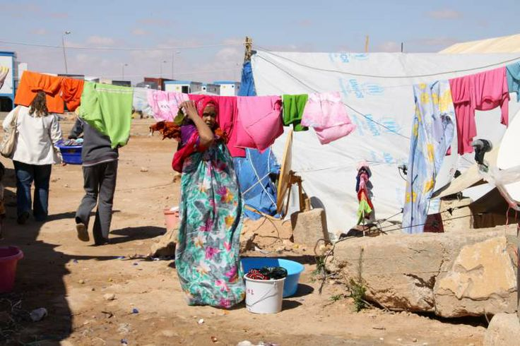 A woman hangs up her family's washing at Sallum beside a shelter made from plastic sheeting and other materials.  ©UNHCR/L. Dobbs