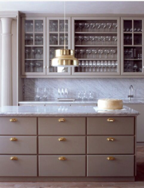 White marble and mushroom colored cabinets. Possibly, antiqued brass fixtures.